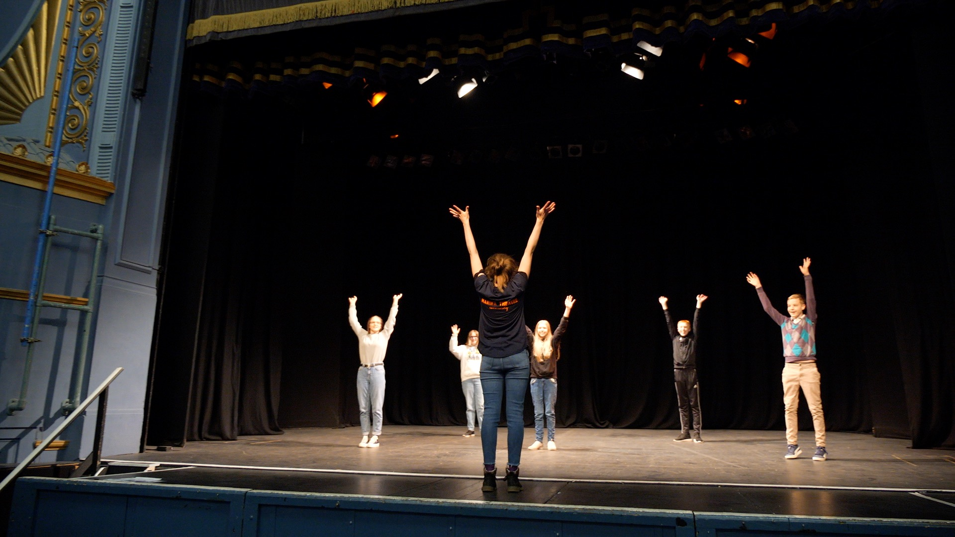 Youth Theatre facilitator leading a physical warm up on stage at the Marina Theatre.